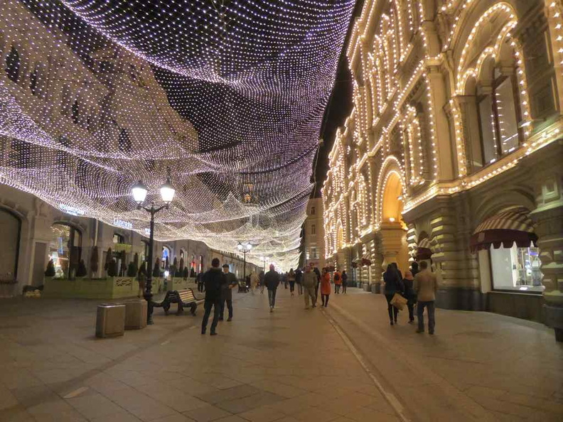 Lights along Nikolskaya street with the lighted GUM  west-facing shop front.
