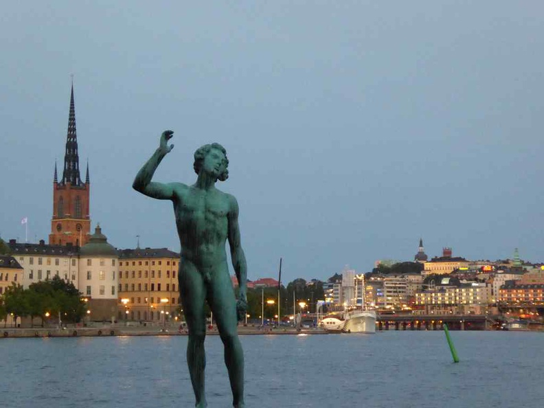 Statues by the Stockholm City Hall, with its spire featuring the golden Three Crowns