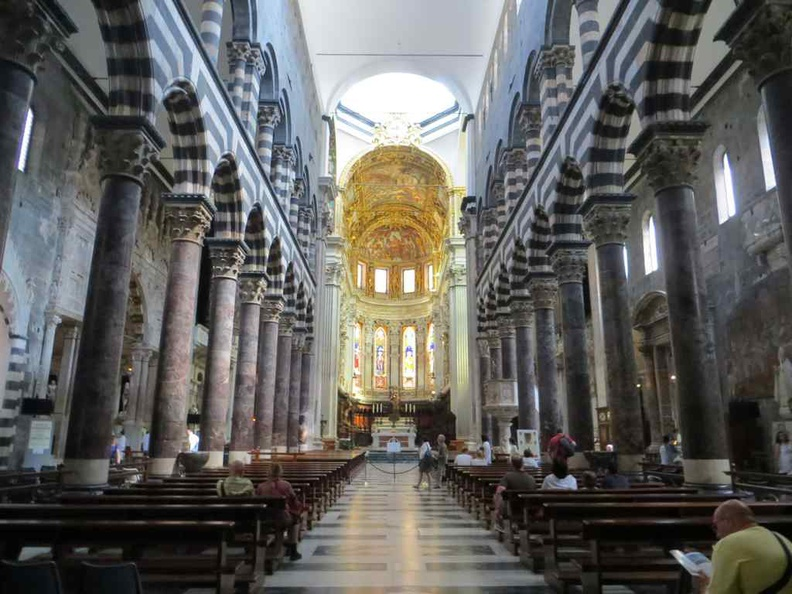 Inside Genoa Cathedral with seating and grand altar