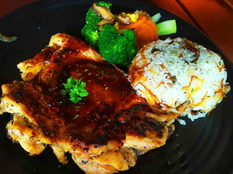 The Grilled chicken dish with rice and vegetable sides