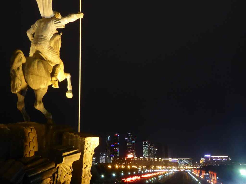 St George statue overlooking the pathway leading to the monument with the city of Moscow lit in the night