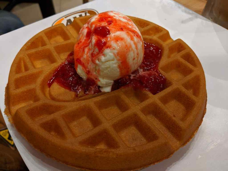 Strawberry waffles dessert, with berry bits and sauce sprinkled over a vanilla ice cream scoop