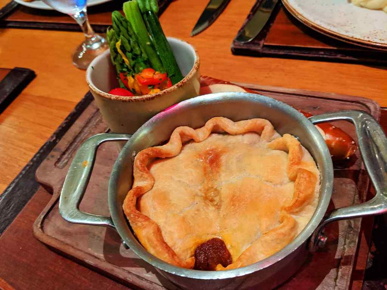 Steak and ale pie with servings of greens