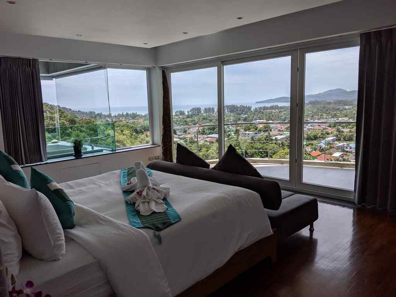 The main master bedroom with a balcony overlooking the distance bay and the infinity pool below