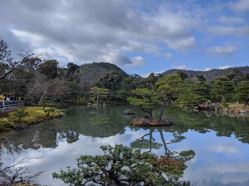 Kinkaku-ji Temple reflecting lake with a hilly background