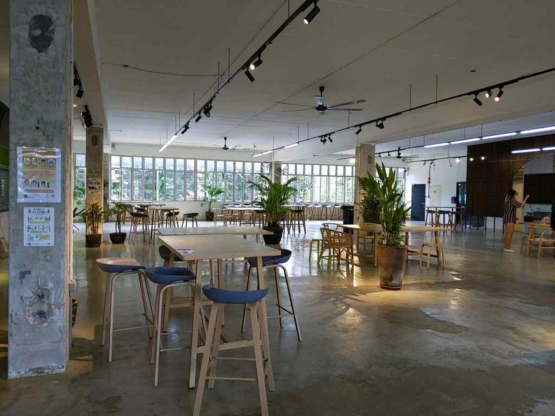 city sprouts sprout hub dining area comprises of a mix of tall and sit-down tables in a non-air-conditioned environment with lots of open ventilation.